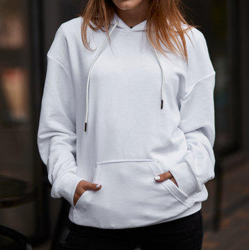 young woman in white hoodie hands in the pockets close up mockup copyspace