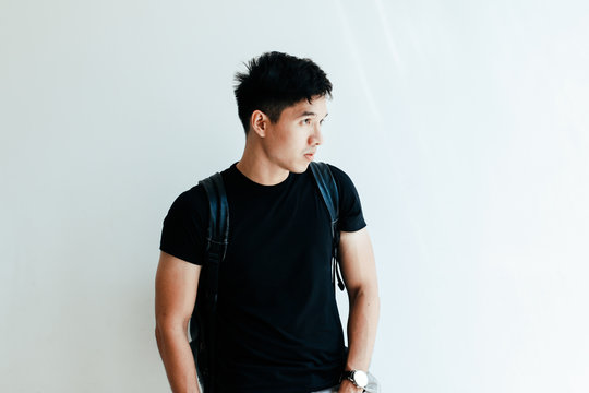 Young handsome asian boy wearing black plain shirt and backpack at day in Sai Gon city, Vietnam - Casual lifestyle of Vietnamese teenager