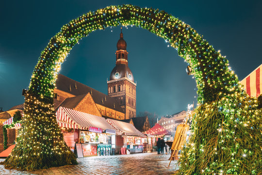 Riga, Latvia. Traditional Christmas Market On Dome Square With Cathedral. Famous Landmark In Winter Evening Night In Festive Illuminations Lighting