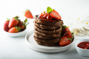 Homemade chocolate pancakes with strawberry sauce