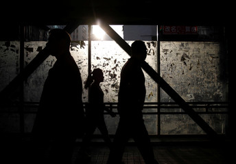 People are silhouetted as they cross a pedestrian bridge in Hong Kong