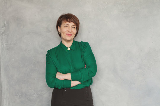 Cute business woman wearing green shirt on gray stucco background, portrait