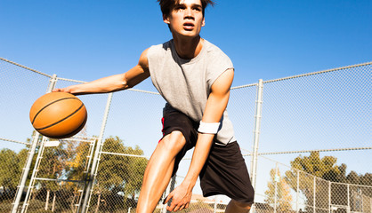 Handsome man playing basketball outside.
