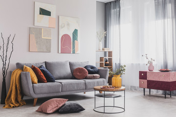 Real photo of abstract paintings hanging on white wall above a gray sofa in a living room interior with big windows