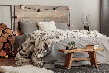 Wooden bench in the foot of the bed with grey bedding and cozy blanket