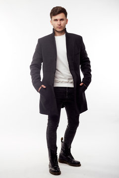 Handsome man in black winter coat, black jeans and boots isolated on white background.