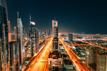 Spoed Fotobehang Dubai Night view of the spectacular landscape of Dubai with high-rises and skyscrapers at the Sheikh Zayed highway. Global travel destinations and real estate concept