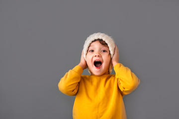 Funny caucasian child in yellow and hat on gray Fototapete