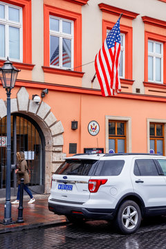 Krakow, poland - APR 30, 2019: American flag on facade of United States Consulate General Krakow located in historic center of an old town. Ford car parked on the wet street on an overcast rainy day