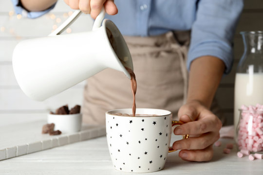 Woman pouring hot cocoa drink into cup on white wooden table, closeup