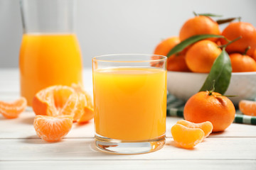 Glass of fresh tangerine juice and fruits on white wooden table
