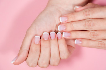 Closeup top view of two beautiful female hands with classic white and pink french manicure at fingernails. Hands isolated on pastel pink background. Horizontal flatlay color photography.