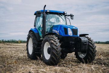 New blue tractor Holland in motion at demonstration field site at agro exhibition AgroExpo. Tractor working on the farm, modern agricultural transport. Kropivnitskiy, Ukraine, September 27, 2018