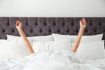 Woman awakening in bed, closeup. Lazy morning