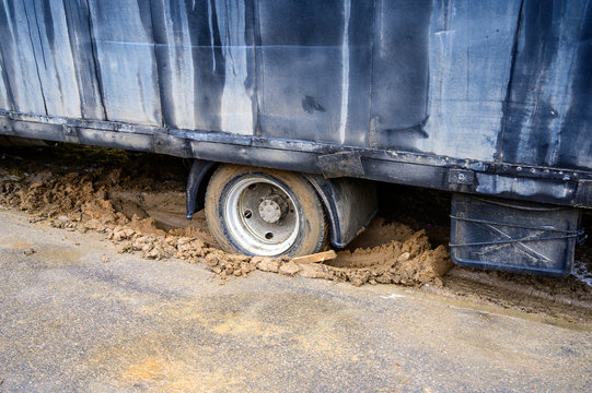 Photo of a heavy truck stuck in mud and skidding in place on a cloudy day.