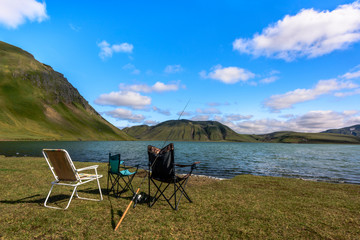 Chairs and fishing rod in front of scenic lake near Landmannalaugar, Iceland