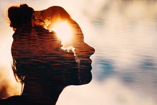 Sun peeks out from behind the clouds in woman's head.