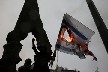 Iranians burn U.S and Israeli flags as they gather to mourn General Qassem Soleimani in Tehran