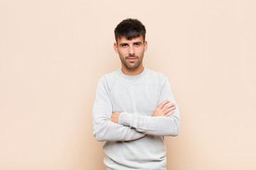 young handsome man feeling displeased and disappointed, looking serious, annoyed and angry with...