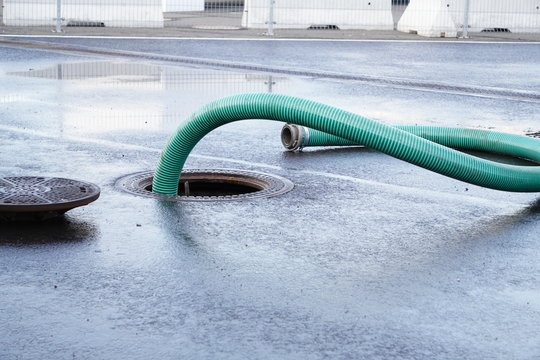 the green thick hose from a sewer pit, pumping sewage or sewage from collector in city. water drainage. Sewer manhole with an open manhole cover and large corrugated suction hoses for waste disposal