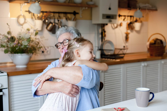 Grandmother hugging child in cozy kitchen at home. Happy family giving thanks. Cute little girl and senior woman is enjoying kindness together. Lifestyle moment. Holiday Thanksgiving.
