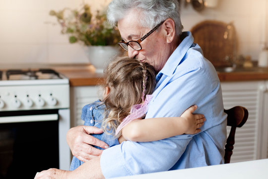 Grandmother hugging child girl. Little kid and senior woman in cozy home kitchen. Happy family enjoying kindness, tenderness. Lifestyle moment.
