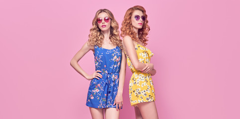 Wall Mural - Fashion. Two beautiful woman in stylish clothes, trendy hair, make up. Adorable embracing shapely sensual model girl, friends on pink. Creative fashionable blonde redhead lovable lady, beauty banner