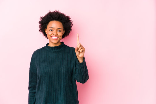 Middle aged african american woman against a pink background isolated showing number one with finger.