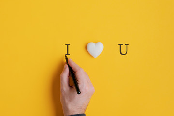 Male hand writing an I love you sign