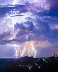 Fototapeta Thunder storm and lightning over hills and city obraz