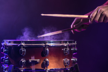 The drummer plays the drums. Beautiful blue and red background, with rays of light. Beautiful special effects smoke and lighting. Process of playing a musical instrument. Close-up photo.