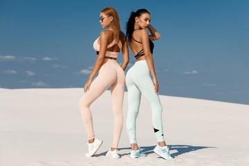Beautiful fitness models in sportswear. Couple athletic girls in leggings outdoor