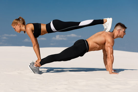 Sporty fitness couple doing planking exercise outdoors. Beautiful athletic man and woman workout