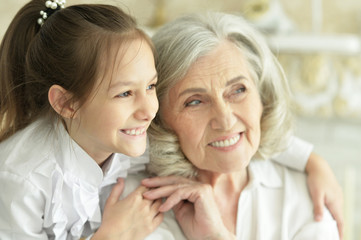 Close up portrait of grandmother with her cute granddaughter smiling