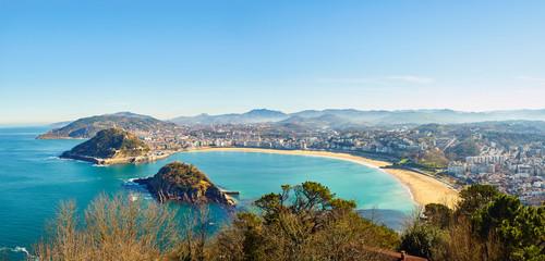 Fototapeta premium Panoramiczny widok na zatokę Concha. Plaża Concha, plaża Ondarreta i wyspa Santa Clara z Monte Igueldo w słoneczny dzień. San Sebastian (Donostia), Kraj Basków, Guipuzcoa. Hiszpania.