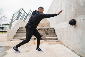 Athletic man doing wall ball exercise. Wall mural