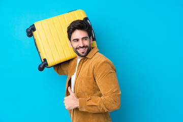 Young handsome man with beard over isolated blue background in vacation with travel suitcase and...