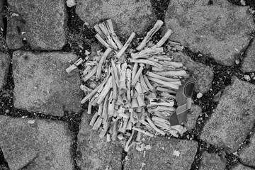 Altenburg / Germany - January 2020: Ashes and paper remains of a firecracker battery on the pavement on New Year's afternoon