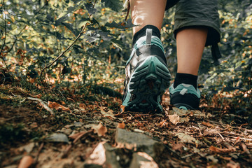 Muddy boots of hiker on forest trail. Traveler feet are stepping on the ground with fallen leaves. Close up of the sole of dirty shoes. Adventure and hiking concept outdoor. Hipster lifestyle