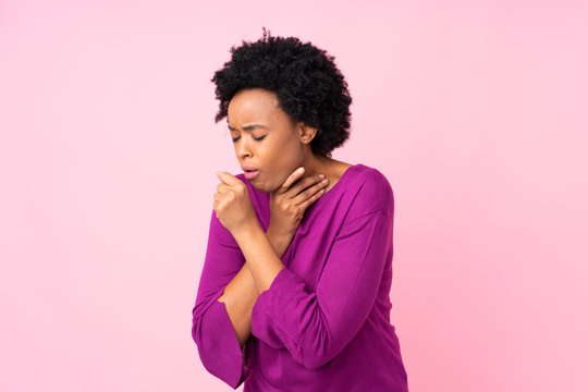 African american woman over isolated pink background is suffering with cough and feeling bad