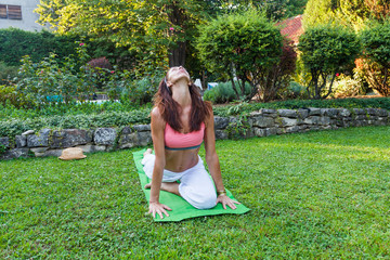 adult woman practice yoga outdoor in garden on grass summer day