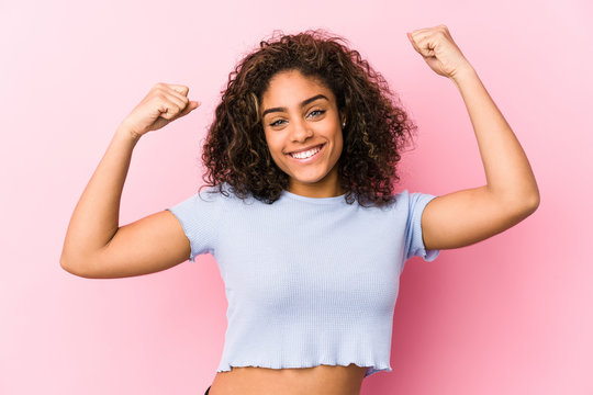 Young african american woman against a pink background showing strength gesture with arms, symbol of feminine power