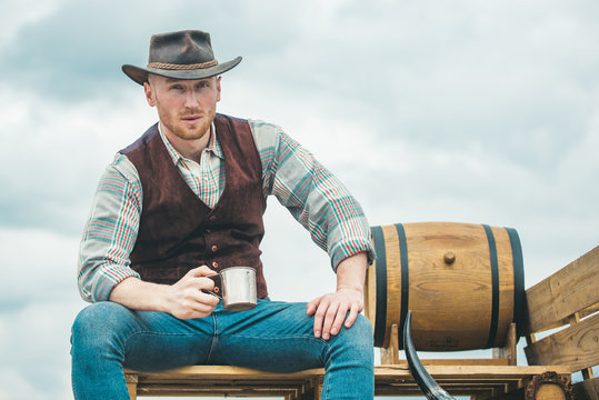 Handsome bearded macho man. Men beauty standard. Example of true masculinity. Cowboy wearing hat. Western life. Unshaven guy in cowboy hat and plaided shirt drinking alcohol.