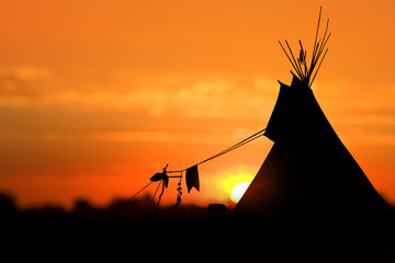An American Indian tipi (teepee) against an evening sunset.
