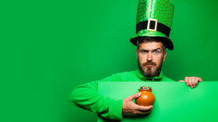 Leprechaun man in green hat and hoodie holding pot of gold. Bearded man wearing leprechaun costume isolated at green background. Bearded man celebrating Saint Patrick's Day.