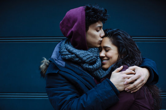 Close up portrait of a happy young hispanic couple embracing each other and kissing on forehead