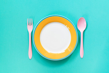 Empty color plates or dish on green table background, top view food concept Fotomurales