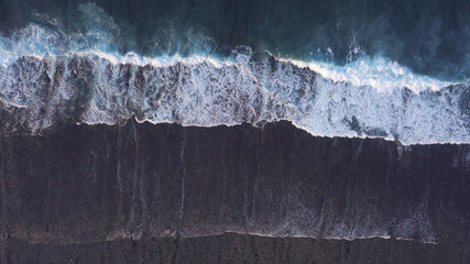 Above the ocean, aerial lock down view at foaming waves and surface near coast line