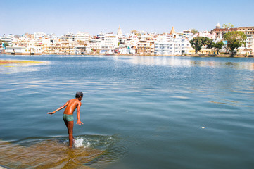 Boy costs in the water of Lake Pichola in Udaipur, India
