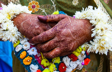 Woman's hands painted with henna mehndi at a traditional Indian wedding in Rajasthan, India